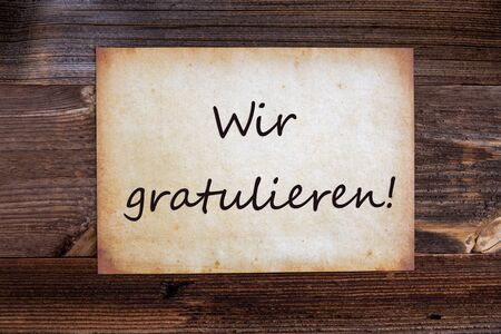 Old Grungy Paper With German Text Wir Gratulieren Means Congratulations. Wooden Background