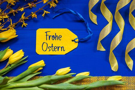 Label With German Text Frohe Ostern Means Happy Easter. Yellow Spring Flowers Like Tulip And Branches. Festive Decoration With Ribbon. Blue Wooden Background
