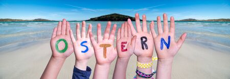 Children Hands Building Word Ostern Means Easter, Ocean Background