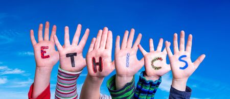 Children Hands Building Colorful Word Ethics. Blue Sky As Background