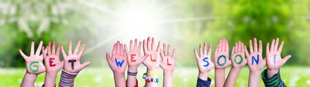 Children Hands Building Colorful English Word Get Well Soon. Sunny Green Grass Meadow As Background Standard-Bild