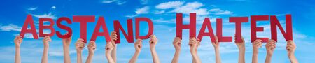 People Hands Holding Colorful English German Abstand Halten Means Keep Distance. Blue Sky As Background