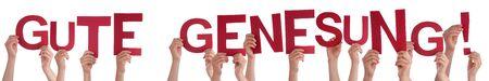 Les gens mains tenant mot Gute Genesung signifie obtenir bien bientôt, fond isolé Banque d'images