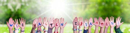 Children Hands Building Colorful German Word Wir Halten Zusammen Means Together We Are Stron. Sunny Green Grass Meadow As Background