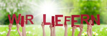 People Hands Holding Colorful German Word Wir Liefern Means Delivery Service. Sunny Green Grass Meadow As Background