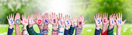 Enfants mains tenant le mot allemand coloré Solidarisch Sein signifie montrer la solidarité. Prairie d'herbe verte ensoleillée comme toile de fond