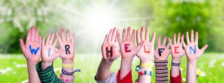 Kids Hands Holding Colorful German Word Wir Helfen Means We Help. Sunny Green Grass Meadow As Background