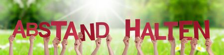People Hands Holding Word Abstand Halten Means Keep Distance, Grass Meadow Banque d'images