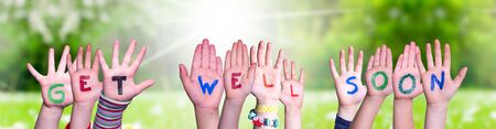 Children Hands Building Colorful English Word Get Well Soon. Sunny Green Grass Meadow As Background Archivio Fotografico