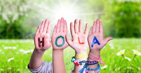 Kids Hands Holding Word Hola Means Hello, Grass Meadow Banco de Imagens