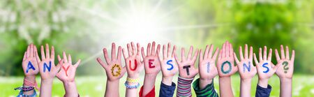 Children Hands Building Colorful Word Any Questions. Sunny Green Grass Meadow As Background