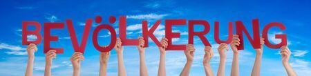 People Hands Holding Word Bevoelkerung Means Population, Blue Sky 免版税图像