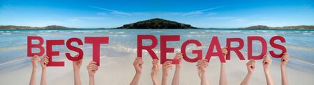 People Hands Holding Colorful English Word Best Regard. Ocean And Beach As Background Stock fotó