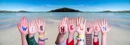 Kids Hands Holding Word Wir Helfen Means We Help, Ocean Background Zdjęcie Seryjne