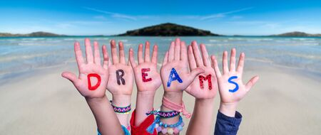 Children Hands Building Colorful English Word Dreams. Ocean And Beach As Background