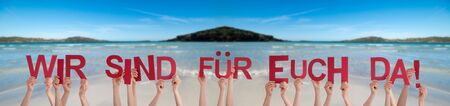 People Hands Holding Colorful German Word Wir Sind Fuer Euch Da Means We Are Here For You. Ocean And Beach As Background Zdjęcie Seryjne