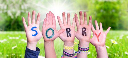 Children Hands Building Word Sorry, Grass Meadow Foto de archivo