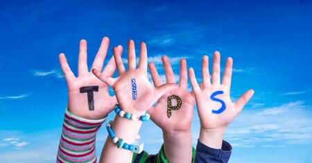 Children Hands Building Colorful English Word Tips. Blue Sky As Background
