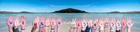Children Hands Building Colorful German Word Wir Haben Geschlossen Means We Are Closed. Ocean And Beach As Background