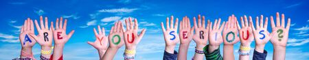 Children Hands Building Colorful English Word Are You Serious. Blue Sky As Background