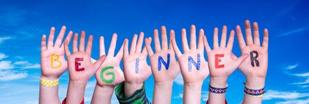 Children Hands Building Colorful English Word Beginner. Blue Sky As Background