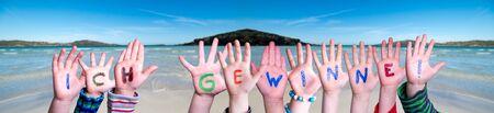 Children Hands Building Word Ich Gewinne Means I Am Winning, Ocean Background