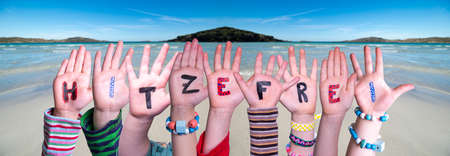 Children Hands Building Colorful German Word Hitzefrei Means Free Due To Excessive Heat. Ocean And Beach As Background