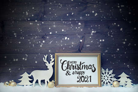 Frame With English Calligraphy Merry Christmas And A Happy 2021. Golden Decoration Like Ball, Tree And Deer. Vintage Wooden Background With Snow