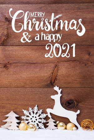 English Calligraphy Merry Christmas And Happy 2021. Christmas Decoration With Tree, Deer And Golden Ball. Brown Wooden Background