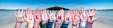 Children Hands Building Colorful German Word Gleichheit Means Equality. Ocean And Beach As Background
