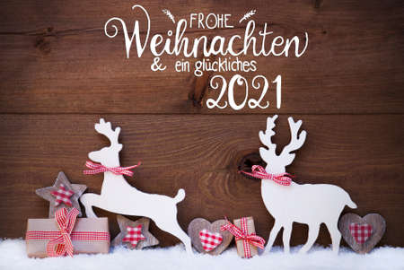 German Calligraphy Frohe Weihnachten Und Ein Glueckliches 2021 Mean Merry Christmas And Happy 2021. Wooden Christmas Ornament Like Present, Heart And Wooden Deer. Wooden Background With Snow Banco de Imagens