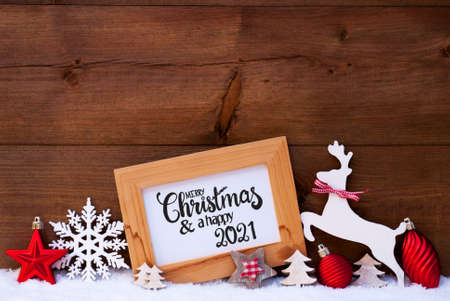 English Calligraphy Merry Christmas And Happy 2021. Red Christmas Ornament Like Tree, Ball And Wooden Deer. Wooden Background With Snow