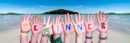 Children Hands Building Colorful English Word Beginner. Ocean And Beach As Background