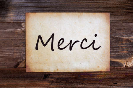 Old Grungy Paper With French Text Merci Means Thank You. Wooden Background 免版税图像