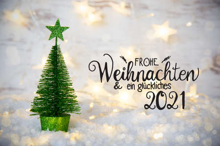 German Calligraphy Frohe Weihnachten Und Ein Glueckliches 2021 Means Merry Christmas And A Happy 2021. One Green Christmas Tree With Star Ornament. Sparkling Lights Background With Snow