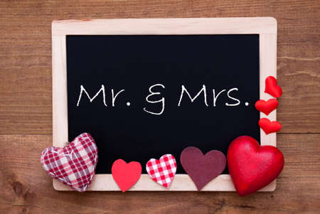Balckboard With English Text Mr And Mrs. Red Heart Decoration. Brown Wooden Background