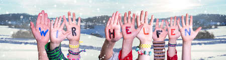 Kids Hands Holding Colorful German Word Wir Helfen Means We Help. Snowy Winter Background With Snowflakes