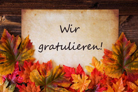 Old Paper With Text Wir Gratulieren Means Congratulations, Colorful Leaves Decoration Zdjęcie Seryjne