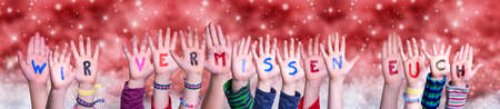 Children Hands Building Colorful German Word Wir Vermissen Euch Means We Miss You. Red Snowy Christmas Winter Background With Snowflakes And Sparkling Lights