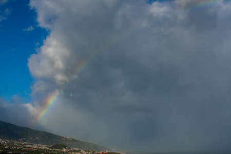 beautiful rainbow over the mountain with clouds