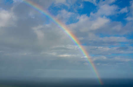 beautiful rainbow over the sea with clouds Stock Photo