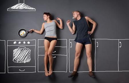 pareja comiendo: chica cocinar el desayuno. amar conjunto historia. todas las im�genes de esta serie ver a mi cartera Foto de archivo