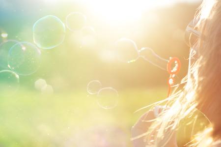 女の子、夏の太陽の肖像画。カラフルな背景 写真素材