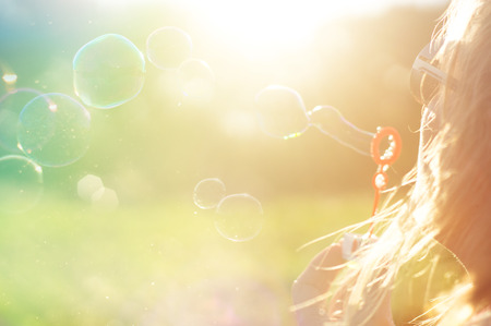 bubbles: girl, portrait in the summer sun. colorful background