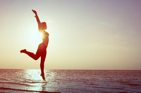 Happy Woman Jumping on the beach. Sea Sunset