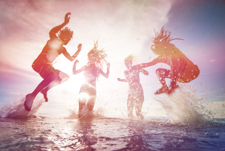 Silhouettes of happy young people jumping in sea at the beach on summer sunset Stockfoto