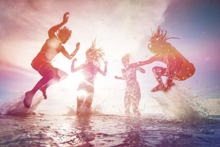 summer: Silhuetas de jovens felizes que saltam no mar na praia no por do sol de verão
