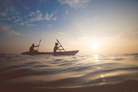 silhouette of a couple on a boat in the sea at sunset