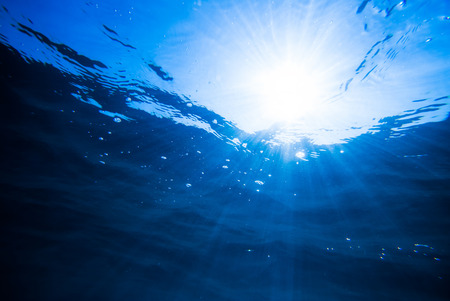 underwater background, deep blue sea with sunrays Standard-Bild