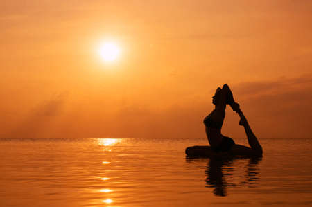 Silhouette young woman practicing yoga on the beach at sunset Standard-Bild
